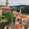"""Ceský Krumlov -- town overview: The castle tower is seen in the upper left. The River Vltava surrounds most of the town in the shape of an exaggerated letter """"S"""""""