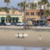 Surfers and jogger on Newport Beach, California