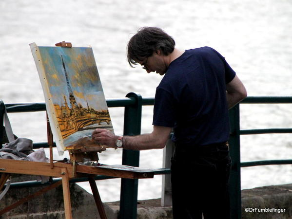 Street artist by the Seine, painting the Eiffel Tower