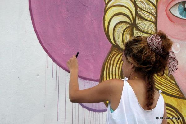 Artists creating street art on Charcarita walls.