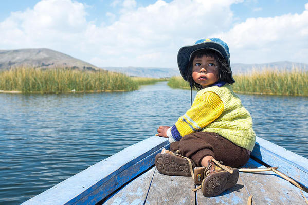 An Uro boy being transported on a boat across Lake Titicaca, courtesy Christopher Crouzet and Wikimedia