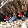 Stanley Glacier.  Sheltering under a large boulder while having lunch and trying to stay dry.
