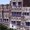 Town houses, Sana'a Yemen made from stone and largely mud and cement then limewashesd around windows and doors to deter insects. The top floor is the mafraj