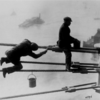 Brooklyn_Bridge_painters_at_work_high_above_New_York_City,_on_03_December_1915