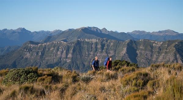 2_paparoa-track-hikers-with-mountain-backdrop