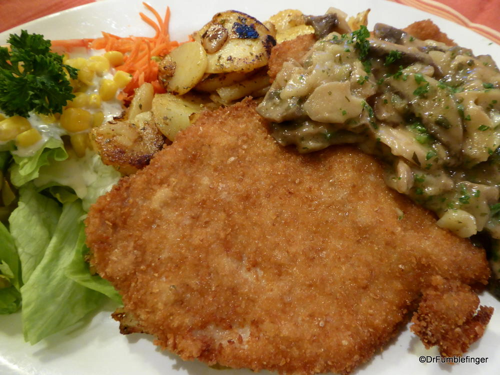 An extremely German meal of Schnitzel, fried potatoes, mushroom sauce and salad.