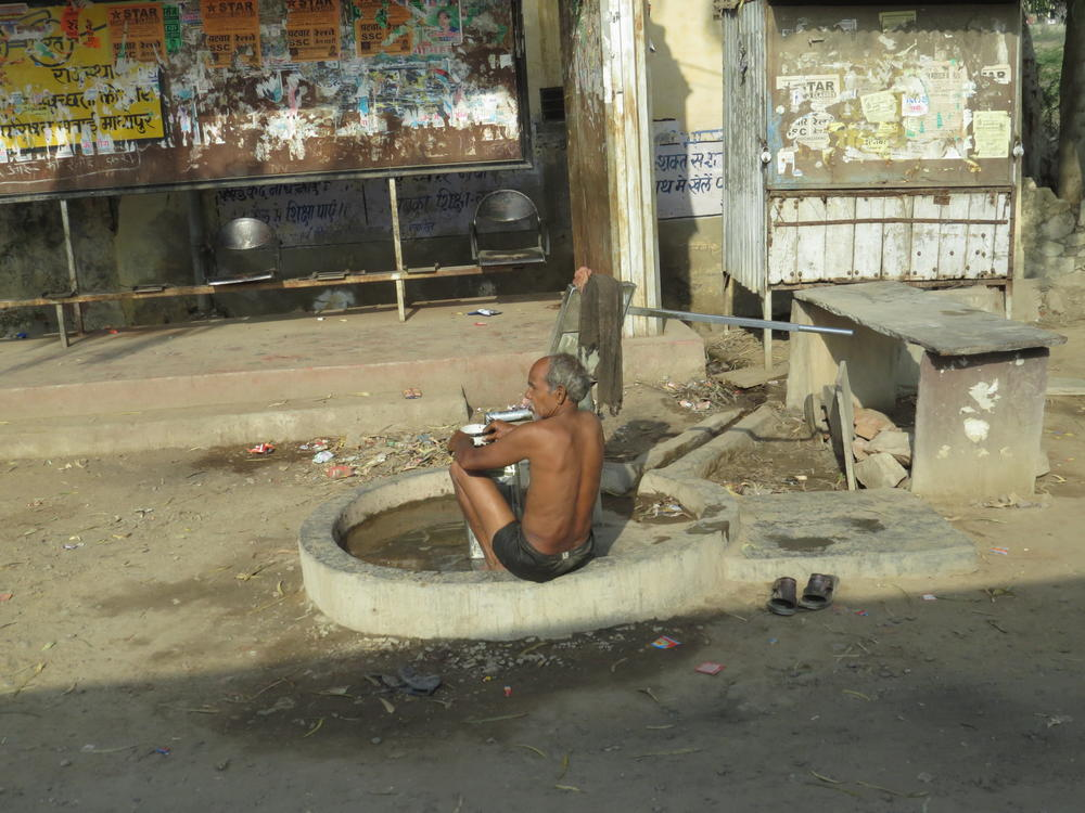 A man bathing near a small water pump, a common scene, Rajasthan