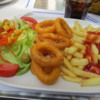 Delicious lunch of fresh calamari rings, fries and a salad