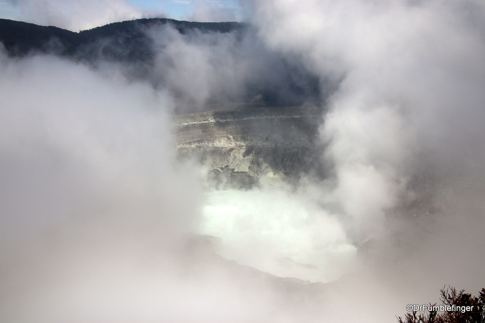 An active volcano, Poas's crater momentarily merges from the Vog